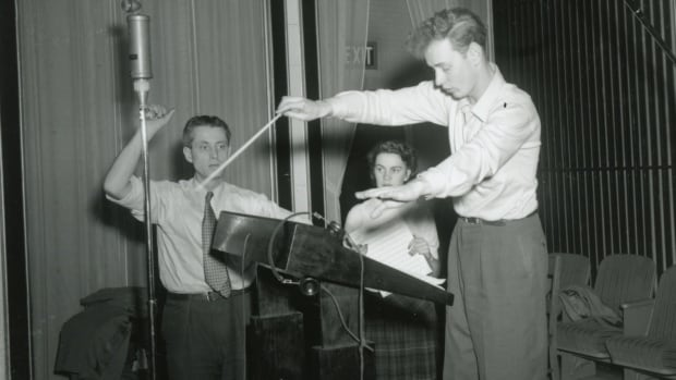 American composer John Williams in 1952 at the Atlantic Films studio on Prescott Street in St. John's. Behind Williams are Ralph Blei, sound engineer, and Margeurite Reid, scriptwriter.