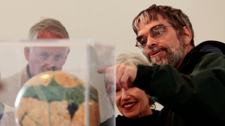 In this April 15, 2011 file photo, Brother Guy Consolmagno, a Jesuit astronomer at the Vatican's Observatory, right, shows to visitors the Globe of planet Mars. (AP Photo/Gregorio Borgia)