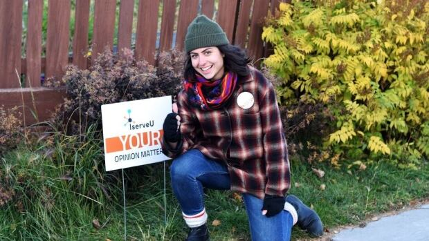 IserveU's volunteer and events coordinator Carly Bradley poses next to one of the group's lawn signs.