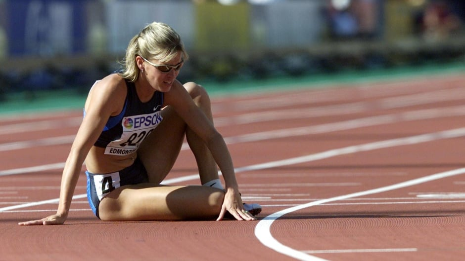 Suzy Favor-Hamilton of the U.S. sits on the track after she fell and did not finish in her heat of the 1500 meter semifinal at the World Championships in Athletics, in Edmonton August 5, 2001.