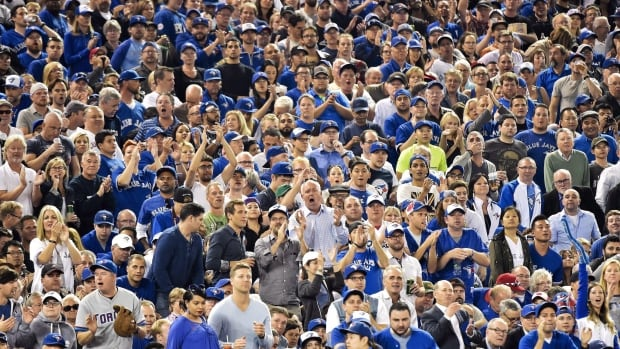Toronto Blue Jays fans stand on their feet cheering as the Jays play against the New York Yankees during seventh inning AL baseball action in Toronto on Wednesday, September 23, 2015. Sick days, last-minute vacation requests and reluctant ticket sales — those were just some of the options being considered by Toronto Blue Jays fans as the baseball team's long-awaited playoff games were officially slated for inconvenient afternoon starts. THE CANADIAN PRESS/Nathan Denette