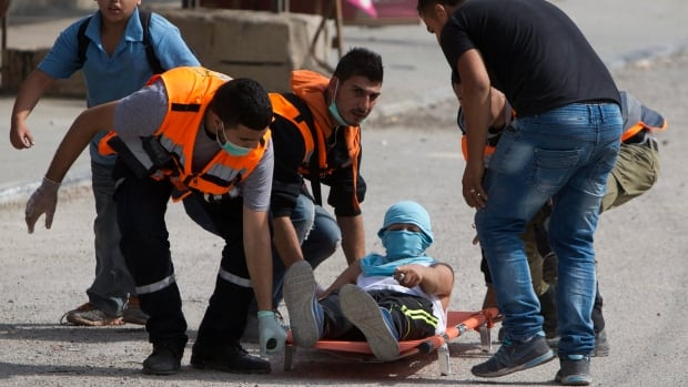 Palestinians carry an injured man during clashes with Israeli troops at Qalandia checkpoint between Jerusalem and the West Bank city of Ramallah on Tuesday. A new generation of angry, disillusioned Palestinians is driving the current wave of clashes with Israeli forces.