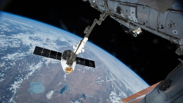 The Canadarm 2 reaches out to capture the SpaceX Dragon cargo spacecraft and prepare it to be pulled into its port on the space station in April 2015. In June, the Harper government made a commitment to extend Canada's participation in the space station until 2024.