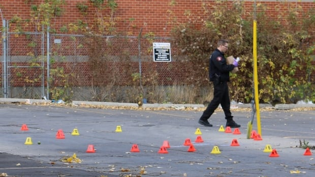 A police officer walks past evidence markers on the ground where a man's body was found.