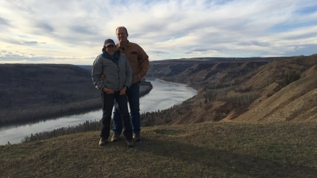 Esther and Paul Pedersen stand on the edge of the farm they stand to lose to the Site C dam, now under construction on the Peace River below.
