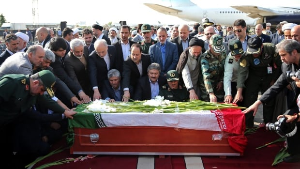Iranian officials pray as they touch the coffin of a dead hajj pilgrim at Mehrabad airport in Tehran on Oct. 3. The pilgrim was killed in a deadly stampede in Mina near Mecca in Saudi Arabia on Sept. 24.