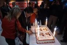Mauril Belanger cutting cake