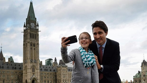 Prime minister designate Justin Trudeau stops to have a selfie taken as he makes his way from Parliament Hill to the National Press Theatre on Tuesday. He said he's determined not to make Canada-U.S. relations a one-pipeline issue.
