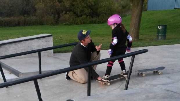 Ryan Carney teaches Peyton Thomas to skateboard in a Cambridge, Ont. park, where she was skating for the first time.