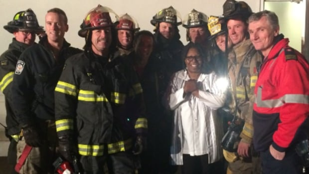 Comedian Whoopi Goldberg poses with members of the Moncton Fire Department after they extinguished a fire on her tour bus parked outside Casino New Brunswick.