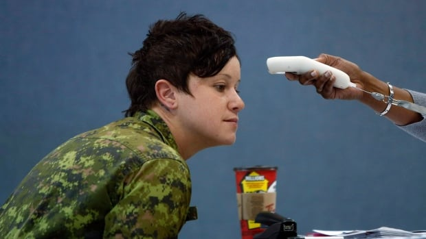 Master Cpl. Lisa Ouellette has her temperature taken during a medical assessment in Ottawa in March. She's one of the more than 5,000 troops from six countries who were deployed to West Africa to help prevent the spread of the Ebola virus.