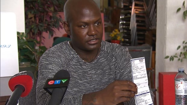 Joel Debellefeuille holds up a ticket he received in Longueuil for driving with a young passenger who was not wearing a seatbelt. He claims he was alone in the car.