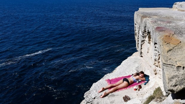 A woman sunbathes on the edge of a cliff at Maroubra beach in Sydney, Australia in a 2013 photo. Southern Hemisphere sunbathers should protect themselves this year, as the ozone hole over Antarctica hit a record size, despite signs that the ozone layer is recovering.