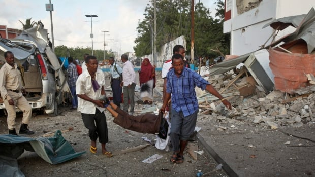 Somali men carry a wounded person to an ambulance outside the Sahafi Hotel in Mogadishu on Sunday after six attackers set off bombs and stormed the compound. The extremist group Al-Shabaab claimed responsibility for the assault.