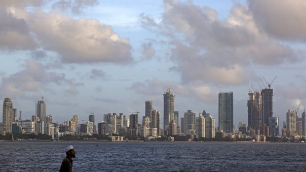 A man walks at the seafront as scattered clouds are seen over Mumbai's skyline.