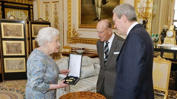 Queen Elizabeth II talks with the Australian High Commissioner Alexander Downer as she prepares to present the Prince Philip, Duke of Edinburgh with the Insignia of a Knight of the Order of Australia, on April 22 in Windsor, England.
