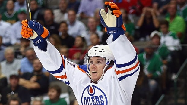 """The Oilers' Connor McDavid, seen here celebrating his first NHL goal on Oct. 13 against the Stars in Dallas, heated up after that performance. On Monday, the 18-year-old centre was named the NHL's rookie of the month after posting 12 points in as many games. """"Now I have a better sense of the tempo the physicality of the game. Just the overall comfort level is the difference,"""" he says."""