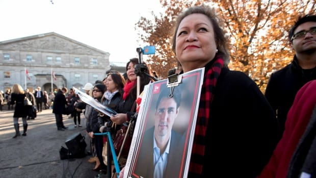 A member of the public holds a Justin Trudeau campaign poster as she waits for the arrival of the new cabinet at Rideau Hall in Ottawa.