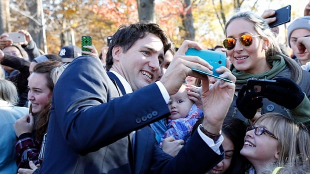 Prime Minister Justin Trudeau takes a selfie wih the crowds outside Rideau Hall after the Cabinet's swearing-in ceremony on Wednesday.