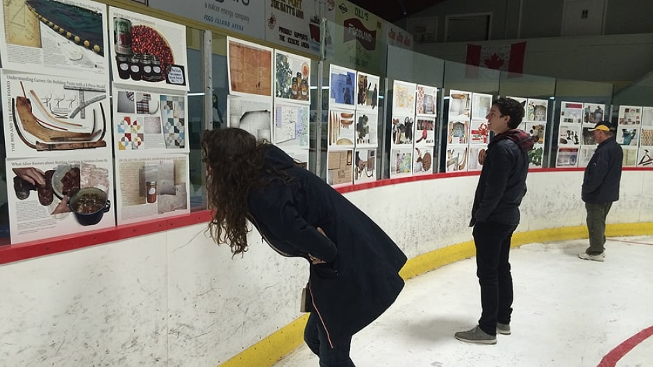 """Visitors view pages from """"The Encyclopedia of Local Knowledge in Fogo"""", on display at the Fogo Island hockey rink."""