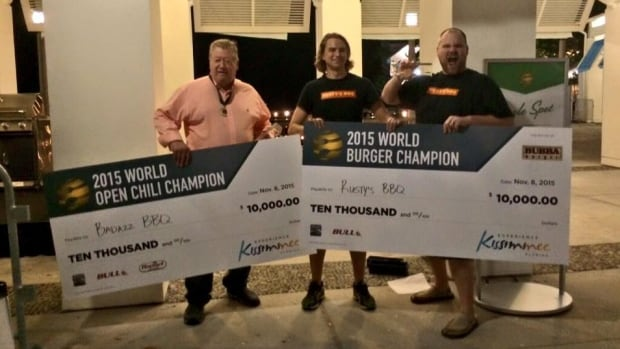 Wayne Shymko, left, holds up his $10,000 US prize cheque from the World Open Chili Championship, which is part of the World Food Championships, in Kissimmee, Florida.