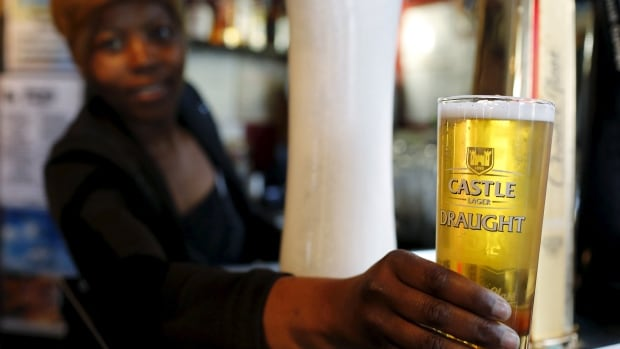 A bartender serves a beer produced by brewing company SAB Miller at a bar in Cape Town, South Africa in September 2015.