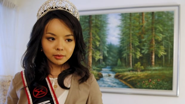 Miss World Canada Anastasia Lin said Tuesday her visa to travel to the beauty pageant at a Chinese resort has been delayed, and her father has been harassed by Chinese officials because she has spoken out about human rights abuses in the country.