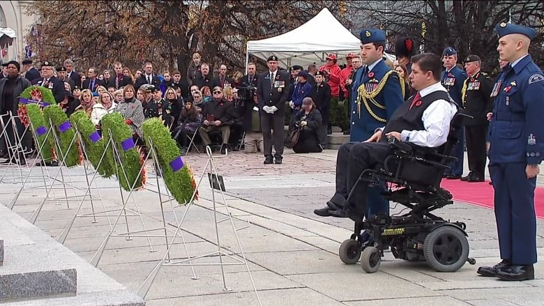 The minister of Veterans Affairs, Kent Heir, is flanked by a military escort  as he lays a wreath at the national war memorial. (CBC)