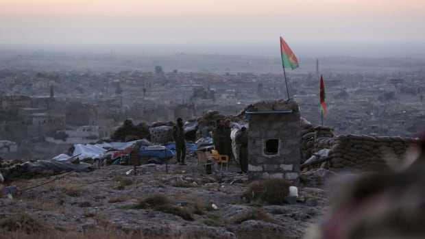 Kurdish fighters watch in the early morning as they battle the Islamic State group in Sinjar, Iraq, on Friday.  Canadian special ops soldiers advising and assisting Kurdish Peshmerga troops in Iraq could be operating near Sinjar's front lines.
