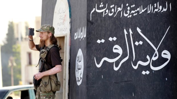 An ISIS member uses his phone to film his fellow fighters taking part in a military parade along the streets of Syria's northern Raqqa province on June 30, 2014.