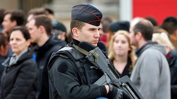A French gendarme patrols in front of the Louvre Museum Monday as it reopens following the deadly series of attacks in Paris on Friday. Armed police and soldiers are now increasingly present in almost every facet of French life.