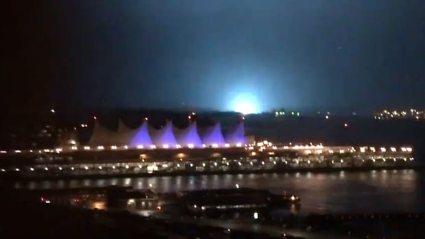 A blue glow fills the night sky as power transformers blow, causing outages on Vancouver's North Shore.