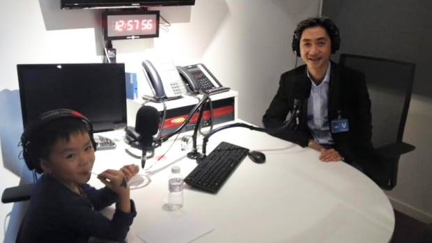 Brandon Le, 6, is seen with his father Angel Le in the Radio-Canada Paris studio discussing the attention they received following their chat about a Paris attacks memorial.