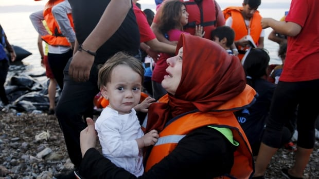A Syrian refugee cries by one of her children as she arrives on the Greek island of Lesbos November 18, 2015. The U.S. has met its target of settling 10,000 refugees from Syria, but the per-capita number accepted by the U.S. remains dwarfed by Canada and some European nations.