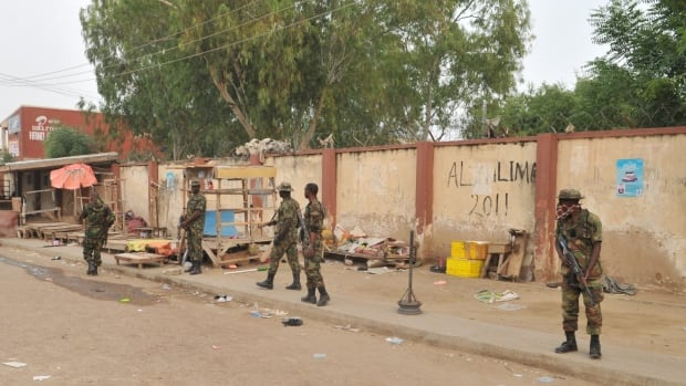Soldiers stand guards at the scene of an  explosion at a market in Kano, Nigeria, on Wednesday.