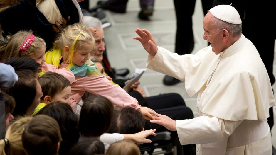 Pope Francis delivers his blessing as children reach out to touch his hand during an audience with members of the Don Guanella charity organization, in the Pope Paul VI hall, at the Vatican, Thursday, Nov. 12, 2015.