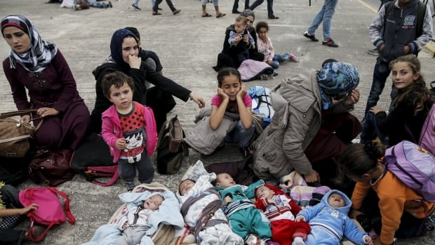 Five Syrian babies, three of them triplets (left to centre), lie on blankets among their relatives as they arrive with other refugees and migrants near Athens in October.