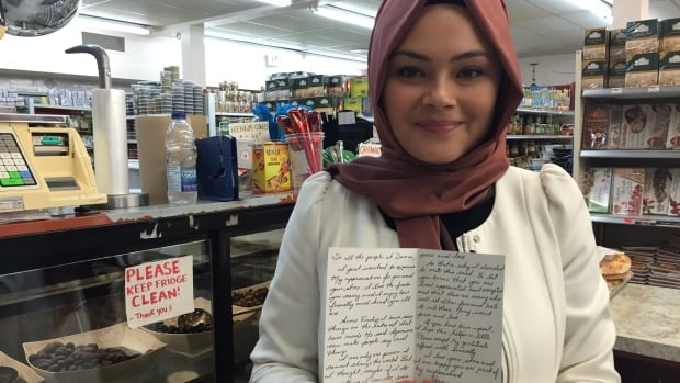 Seyma Elevli shows the supportive card she and her family received at their Carling Avenue grocery store on Tuesday.