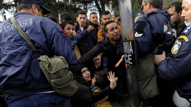 Police push back a group of migrants stalled at the Greek-Macedonian border near the village of Idomeni, Greece, on Sunday.