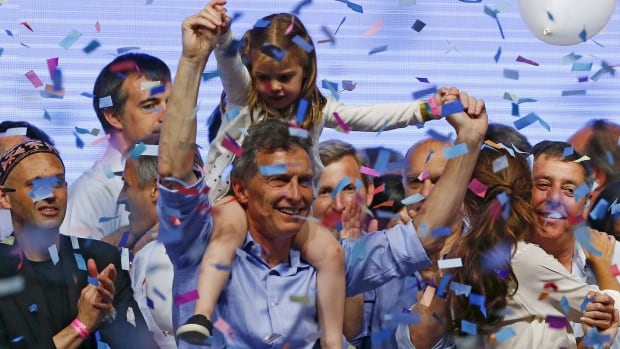Mauricio Macri, presidential candidate of the Cambiemos (Let's Change) coalition, carries his daughter Antonia on his shoulders Sunday as he celebrates with supporters after the presidential election in Buenos Aires.