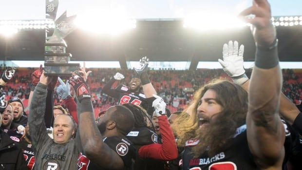 Ottawa Redblacks head coach Rick Campbell, left, hoists the East Division trophy as players celebrate following their win over the Hamilton Tiger-Cats in the CFL East final at TD Place in Ottawa on Nov. 22, 2015.