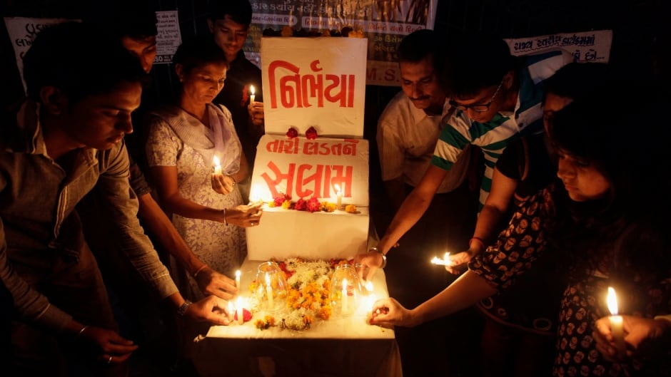 "Indians place candles as they remember the gang rape and murder of a young woman in New Delhi, India. The victim, a 23-year-old physiotherapy student, was heading home with a male friend after an evening showing of the movie ""Life of Pi"" when six men lured them onto a private bus. With no one else in sight, they beat the man with a metal bar, raped the woman and used the bar to inflict massive internal injuries. Placard in center reads, ""Nirbhaya, or fearless, a name given to the victim by the media, salute to your fight""."