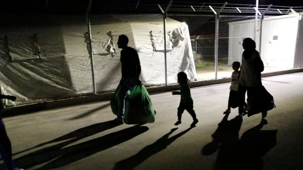 A migrant man and woman with two children arrive at a refugee camp housing facility Nov. 19, 2015.