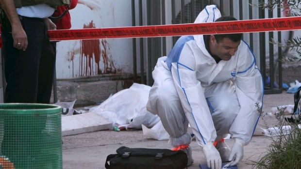 An Israeli policeman collects evidence next to the body of an Israeli soldier killed in a stabbing attack at a West Bank petrol station near Jerusalem, on Nov. 23, 2015.