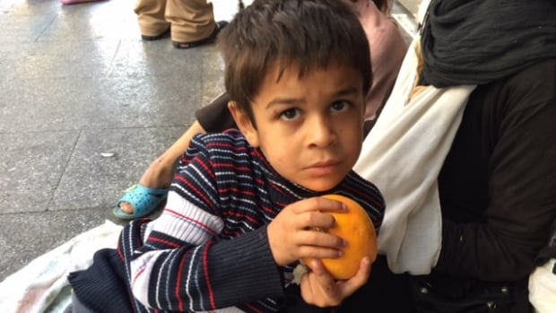 A young Syrian refugee clutches his treasure — an orange — as his mother begs on the streets of Beirut. As many as 1.2 million refugees have flooded into Lebanon from neighbouring Syria as the conflict rages there.