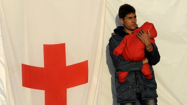 A man holds a baby outside a Red Cross tent in a refugee camp in Greece. In Canada, the Red Cross is hoping concern for refugees will drive its holiday donations this year.
