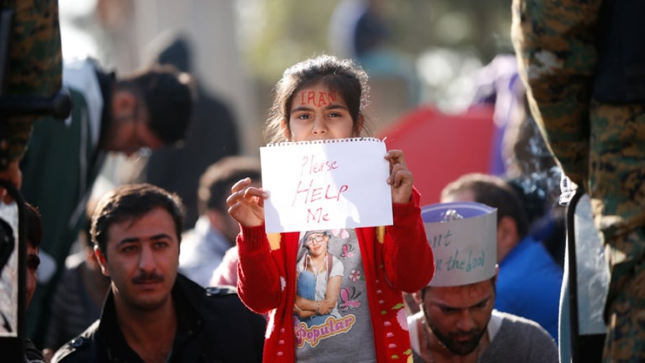 A migrant's child holds a paper with text 'Please Help Me' as she waits to cross the border from Greece into Macedonia, near Gevgelija, Macedonia November 24, 2015.
