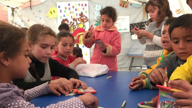 Syrian children colour and draw pictures in a classroom at the Saad Nayel drop-in centre in Lebanon.