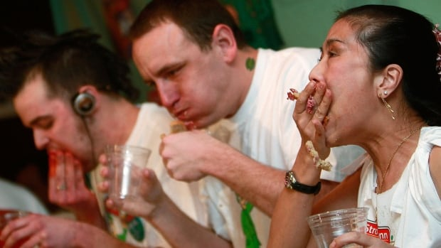NEW YORK - MARCH 16:  Competitive eaters (L-R) Pat Bertoletti, Joey Chestnut and Juliet Lee face off in the first-ever Stroehmann Sandwich Slamm, an eating contest featuring corned beef and rye sandwiches ahead of St. Patrick's Day, March 16, 2009 in New York City. Winner Pat Bertoletti consumed 16 3/4 sandwiches in ten minutes to win the contest at Gallagher's Steakhouse.