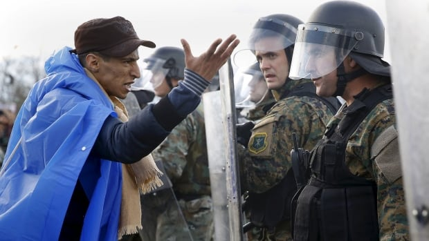 A stranded Moroccan migrant argues with Macedonian police during clashes as hundreds of stranded people tried to cross the Greek-Macedonian border near the Greek village of Idomeni on November 26, 2015.